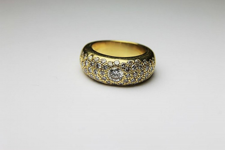 BAGUE jonc la monture en or jaune pavée de diamant retenant en son centre un diamant de taille brillant. Poids brut : 14,6 g TDD : 53