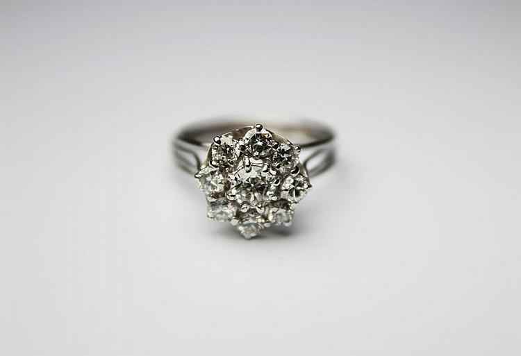 BAGUE en or gris ornée en son centre d'un diamant rond dans un entourage de diamants de taille brillant. Poids brut : 4,5 g TDD : 56 - 57