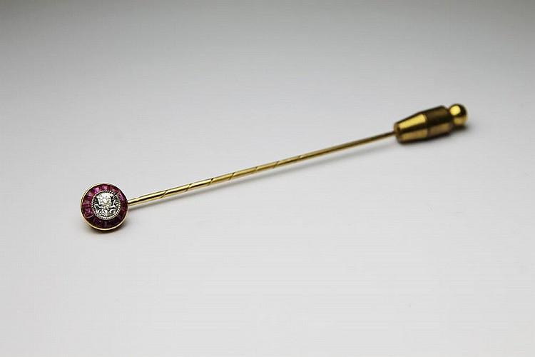 EPINGLE DE CRAVATE en or jaune ornée d'un diamant de taille brillant dans un entourage de rubis. Poids brut : 3,7 g