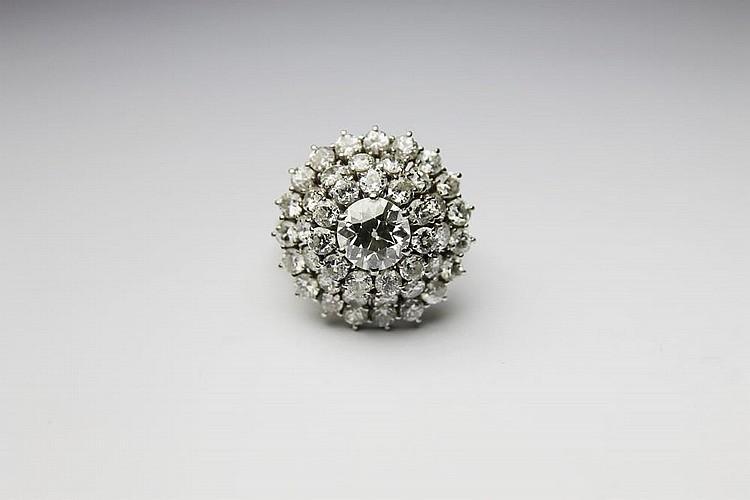 BAGUE en or gris ornée d'un diamant de centre dans un triple entourage de diamants de taille brillant. Poids brut : 6, 5 g TDD : 53