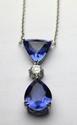 PENDENTIF et sa chaine en or gris orné de deux tanzanites environ 10 carats en chute de taille triangulaire et poire, ponctué d'un diamant de taille brillant. Poids brut : 6,8 g