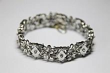 BRACELET en or gris ciselé, composé de losange sertis de diamants de taille brillant et de maillons à motif floral sertis de diamants de taille brillant. Poids brut: 33,9 g