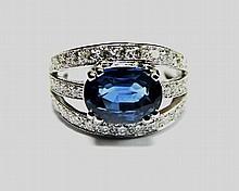 BAGUE en or gris ornée d'un saphir de taille ovale de 3.80 carats, la monture composée de trois anneaux réhaussés de 36 diamants de taille brillant pesant 1.05carat. Poids brut: 7,30 g TDD : 50.5