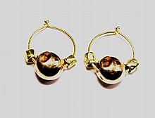 POMELLATO PAIRE DE BOUCLES D'OREILLES en or jaune composée de petites créoles retenant une perle en or rose gravée au motif du Dodo, entourée de deux perles d'or jaune. Poids brut: 9,3 g