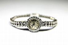 MONTRE en or gris ornée d'un cadran rond, le bracelet composé d'une double succession de diamants de taille brillant en serti clos. Poids brut : 22,3 g