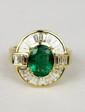 BAGUE en or jaune ornée d'une émeraude de taille ovale de 1,75 carats dans un entourage de diamants de taille baguette. Poids brut : 7,9 g TDD : 54