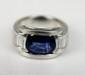 BAGUE style Art Déco en or gris ornée d'un saphir de taille ovale de 2,95 carats épaulé de de cinq diamants de taille baguette. Poids brut : 11,95 g TDD : 51  A sapphir, diamond and white gold ring.