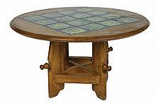 Robert GUILLERME (1913-1990) et Jacques CHAMBRON (1914-2001) Table guéridon à système (position haute et basse) en chêne, plateau orné de 16 carreaux de céramique émaillée bleu-vert Circa 1960 H : 52 cm - Diam.: 92 cm