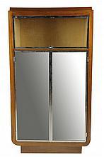 TRAVAIL MODERNISTE des ANNÉES 1930/35 Cabinet, de forme quadrangulaire reposant sur un socle en retrait, réalisé en placage de palissandre. La façade s'ouvre par deux portes pleines, à fond de miroir enchâssé dans un encadrement en métal chromé,