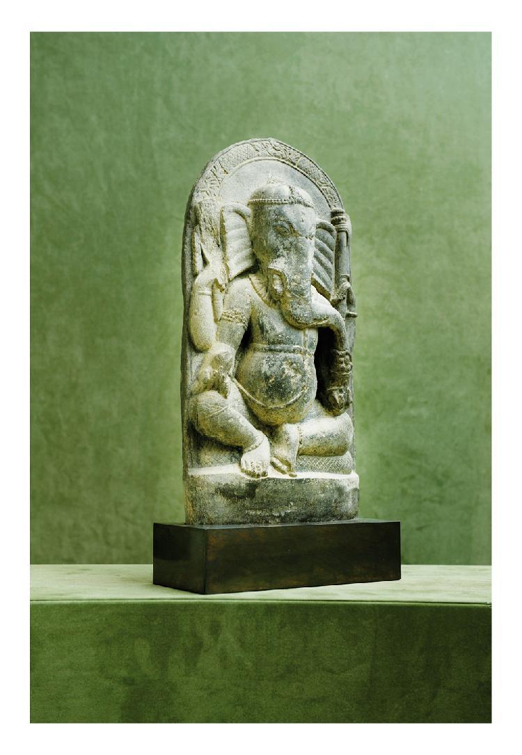 Inde du sud. 14ème siècle. Stèle en schiste sculpté de ganesh assis tenant ses attributs. Art dravidien, H. 44 cm.