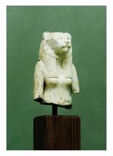 égypte, XXIIèmedynastie Bubastis probablement.   HAUT D'UNE  STATUETTE représentant Bastet, maîtresse de Bubastis sous la forme d'une déesse à tête de lionne. Faïence vert clair. Inscrite sur le dosseret.  Usures.  H. 11,8 cm