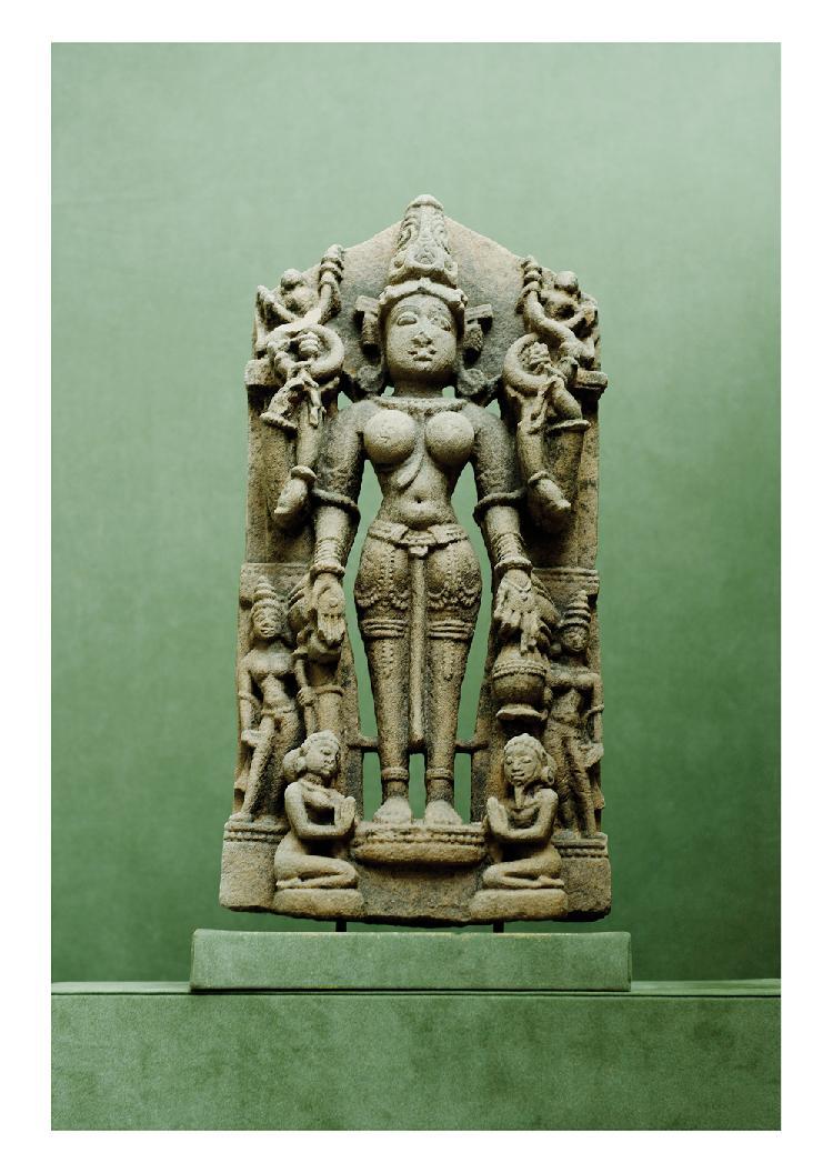 Indes 13ème siècle. Stèle en grès gris sculpté de Parvati à quatre bras entourée de divinités féminines et servante agenouillées. H. 50 cm.