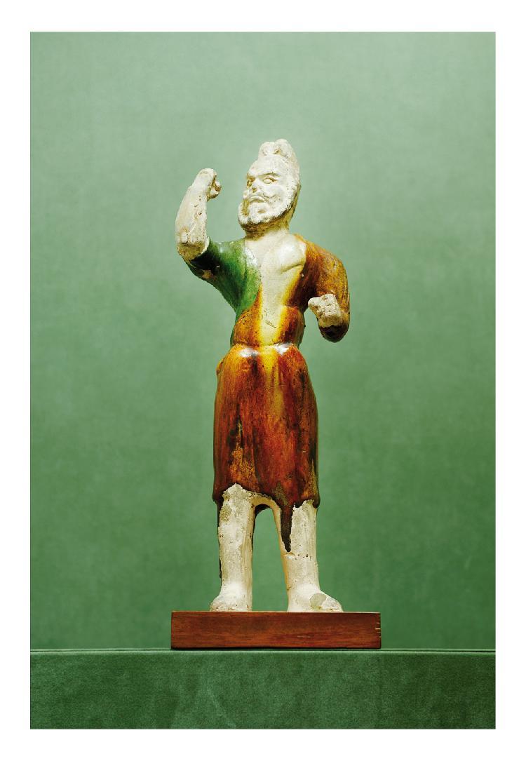 Chine époque Tang. Statuette de chamelier debout en terre cuite émaillée vert, brun et beige. (Restaurations). H. 45 cm.