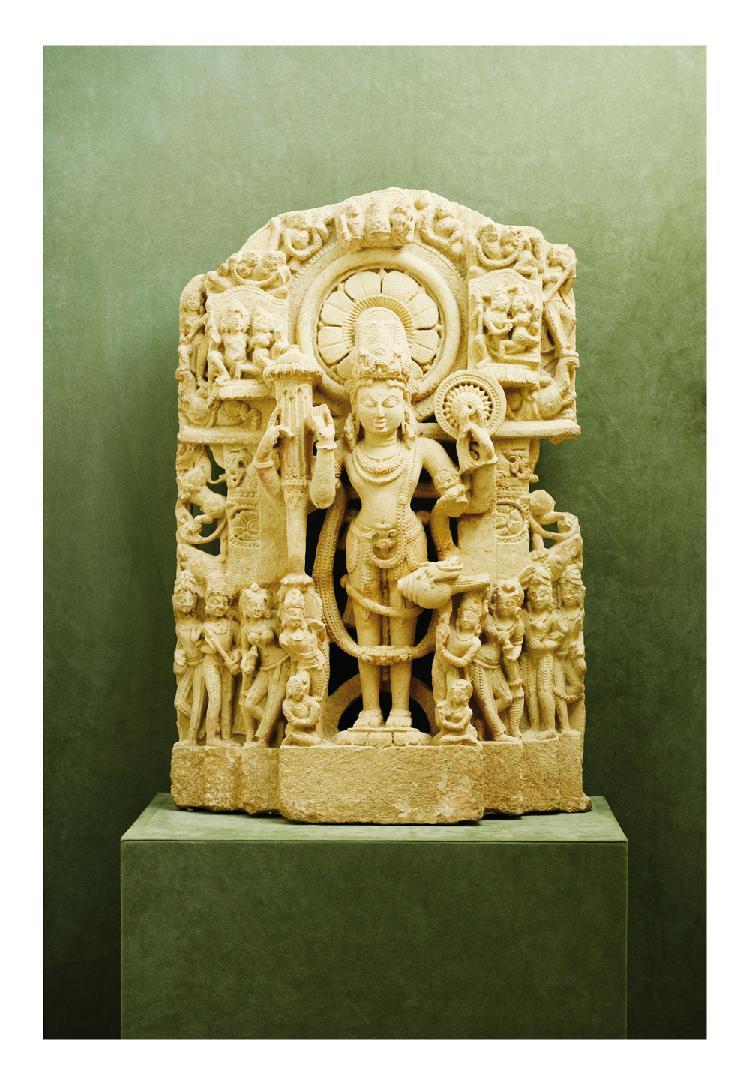 Inde 13ème siècle. Stèle en grès gris clair sculpté de vishnu debout entouré de danseuse et apsara. H. 74 cm.