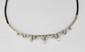 RAVISSANT COLLIER en or gris orné d'un décors de volutes serties de diamants, retenant en pampille trois diamants de taille brillant. Mailles briquettes. Environ 3 carats de diamants. Poids brut : 37,7 g