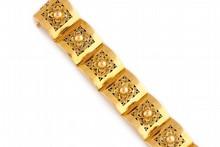 BRACELET manchette en or jaune à maillons articulés   décorés de motifs floraux ciselés et ajourés en fils d'or.    Poids brut : 86,7 g     Longueur : 17,4 cm    A YELLOW GOLD BRACELET