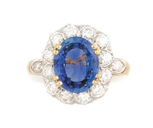 BAGUE marguerite en or gris et or jaune ornée d'un saphir de taille ovale de 5.33 carats dans un entourage de douze diamants de taille brillant pesant 0,80 carat, la monture réhaussée de deux diamants de taille brillant. Poids brut: 8,70 g TDD : 56 A
