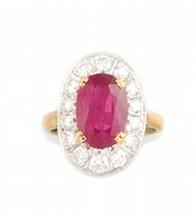 BAGUE en or gris et or jaune de forme ovale ornée d'un rubis taille ovale de 4.60 carats dans un entourage de quatorze diamants de taille brillant pesant 0.95 carat. Poids brut: 8,5 g TDD : 53 A RUBY, DIAMOND, WHITE AND YELLOW GOLD RING.