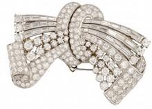BROCHE transformable en deux clips de revers, en or gris et platine stylisant un ruban noué entiÈrement serti de diamants de taille brillant et de taille baguette. Longueur : 6,5 cm Largeur : 4,5 cm Poids brut : 40,9 g A WHITE GOLD, PLATINIUM AND D