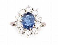 BAGUE en or gris ornée d'un saphir de taille ovale d'origine Ceylan dans un entourage de dix diamants de moderne d'environ 0,10 carat. Poids brut : 4,1 g TDD : 48  A sapphire and diamond white gold ring