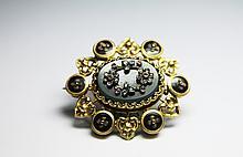 BROCHE en or jaune ornée en son centre d'un japse sanguin ponctué de fleurs serties de diamants de taille rose et de pierres de couleur rouge, dans un entourage stylisé de six macarons émaillés. Poids brut : 14,3 g Hauteur : 4,8 cm largeur : 4 cm