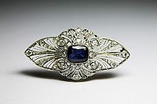 BROCHE en platine et or jaune ornée d'un saphir en son centre de taille coussin, la monture ajourée et sertie de diamants de taille rose et de taille ancienne Poids brut : 9,8 g
