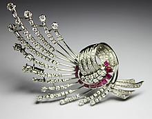 BROCHE en or gris stylisant un important motif en volute serti de diamants de taille brillant et de rubis de taille émeraude. Poids brut : 40,9 g Hauteur : 9,5 cm