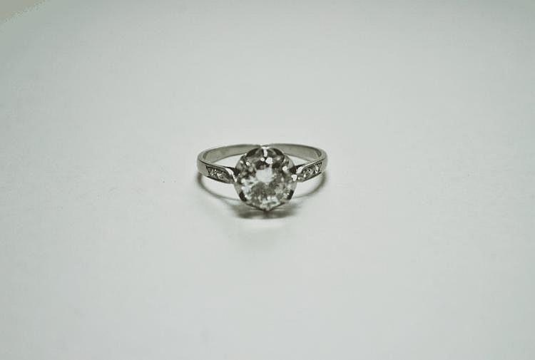 BAGUE SOLITAIRE en or gris ornée d'un diamant de taille brillant de 1,20 carat épaulé de diamants de taille brillant.  Poids brut : 3,3 g TDD : 55
