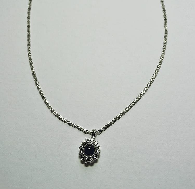 PENDENTIF et sa chaine stylisée en or gris, orné d'un saphir de taille cabochon dans un entourage de diamants de taille brillant.  ( environ 1,60 carats). Poids brut : 13,3 g
