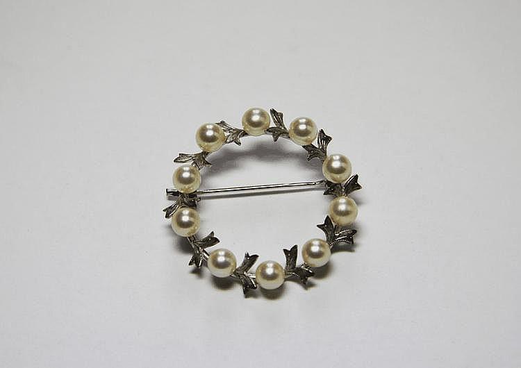 BROCHE en or gris ornée de perles.  Poids brut : 5,4 g