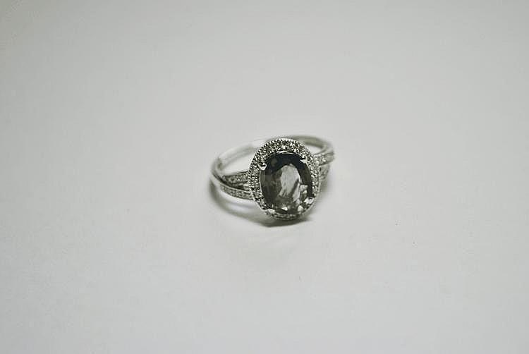 BAGUE en or gris ornée d'un saphir taille ovale de 2,60 carat dans un entourage de diamants de taille brillant. Poids brut : 3,6 g TDD : 54. Avec son certificat AIGS attestant sans modification thermique