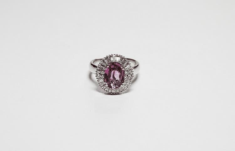 BAGUE en or gris ornée d'un saphir rose de 2,30 carats de taille ovale dans un entourage de diamants de taille baguette et quatres diamants de taille moderne.  Poids brut : 6,8 g TDD : 54