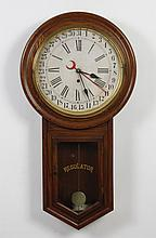 WATERBURY REGULATOR WALL CLOCK - Eight day spring mechanism; having an oak case with round face, brass bezel; Roman and Arabic numbe...