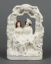19TH CENTURY STAFFORDSHIRE FIGURINE - Portrays a Scottish courting couple under a grape arbor. Cream colored with cold paint accents...