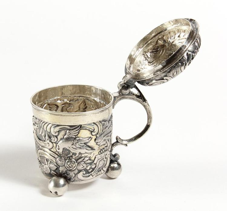 18TH CENTURY RUSSIAN SILVER TANKARD - Moscow 1762 - Silver lidded tankard with floral and eagle imagery in relief on textured bases....