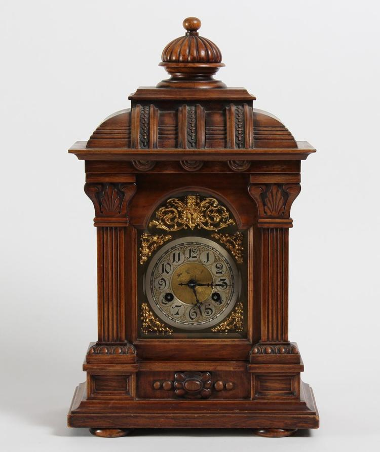 JUNGHANS MANTEL CLOCK - German. Walnut case with half columns and rolled upper section with dome finial. Metal face with cut brass d...
