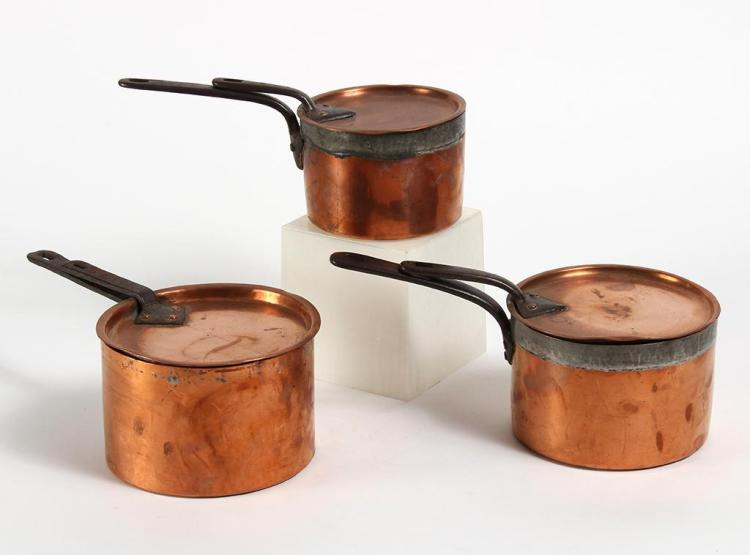 THREE JONES BROS COPPER SAUCEPANS WITH COVERS - Tin lined interior and outer edge on two sauce pans; iron handles on covers and pans...