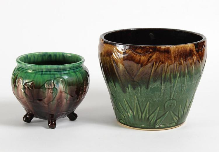 TWO WELLER POTTERY JARDINIERES - First, footed with blended green and brown drip glaze; having 2 white amorphous portrayals of human...