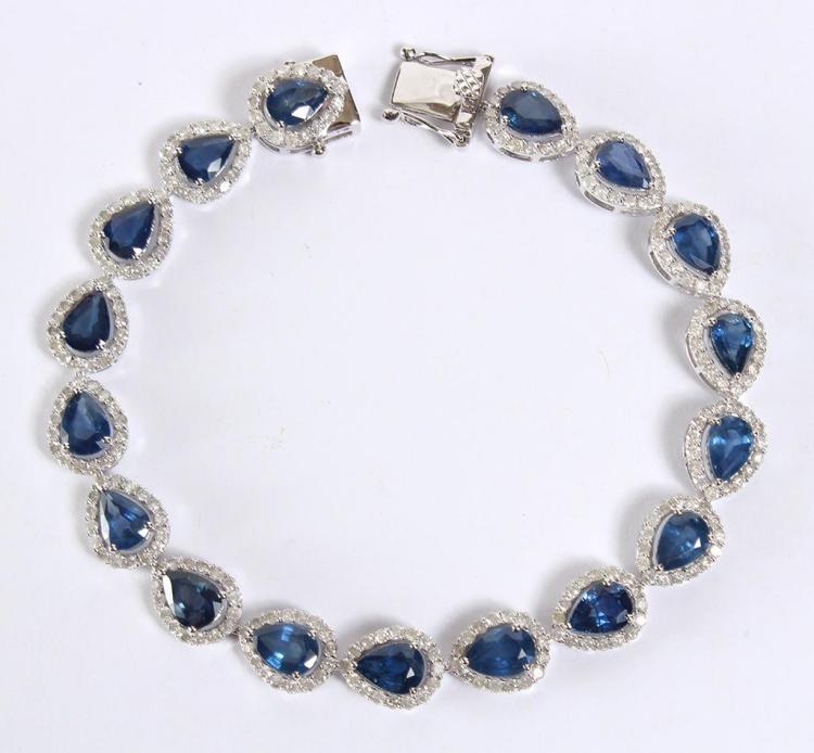 SAPPHIRE & DIAMOND 14KT GOLD BRACELET - A flexible ribbon of 17 prong set, pear cut natural blue sapphires set within 17 diamond bez...