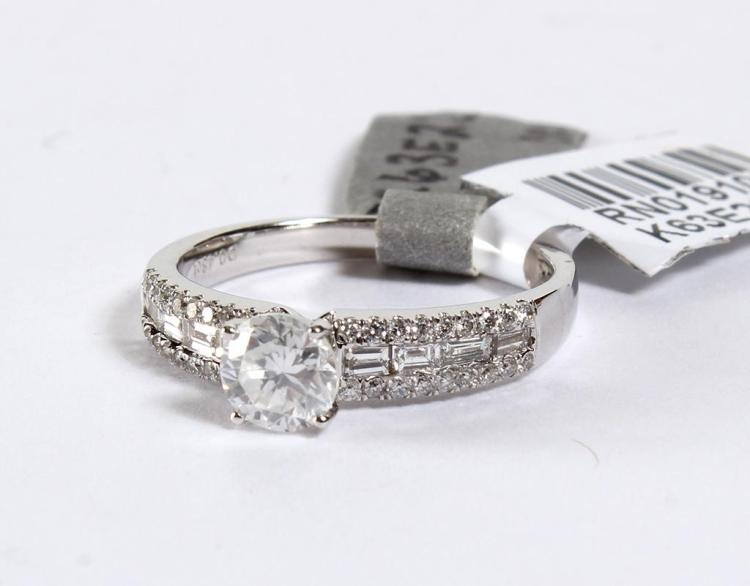 18 KT GOLD DIAMOND UNITY RING - An 18 kt white gold mounting features a 0.70 ctw prong set round brilliant cut diamond of S1-3 clari...