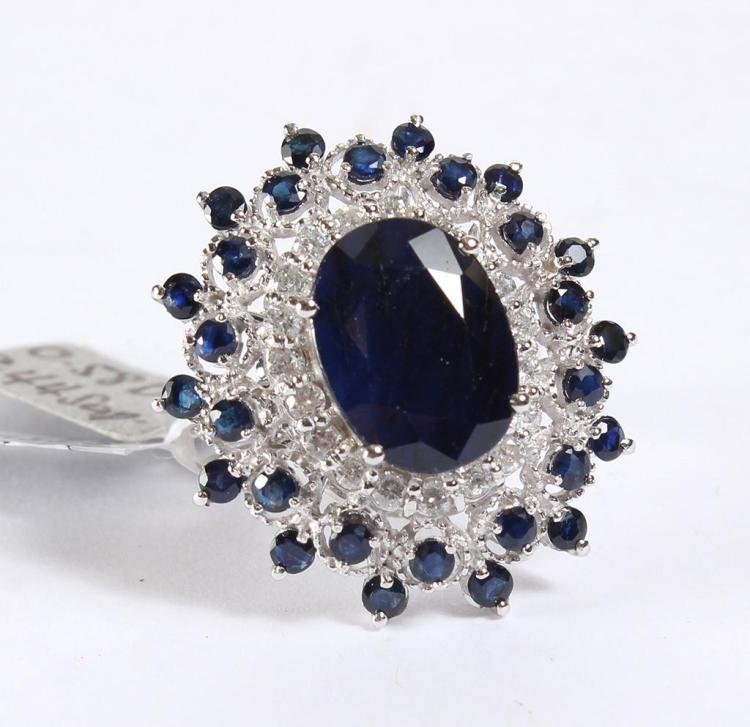 BLUE SAPPHIRE & DIAMOND RING - An oval cut medium blue sapphire gemstone is prong set in the 14 kt white gold mounting. Round brilli...