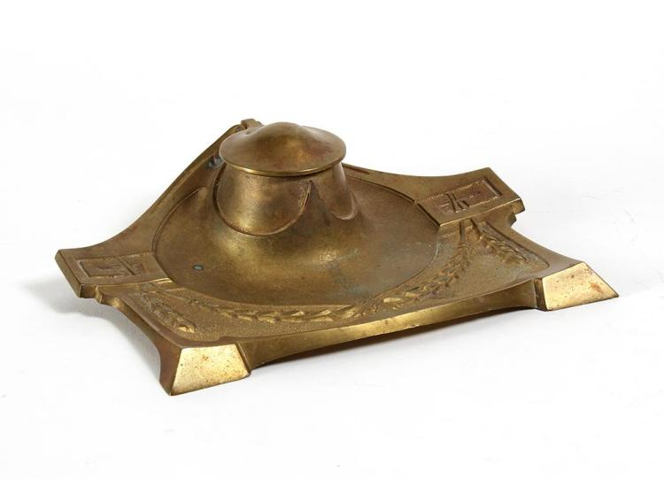 CAST GILT BRONZE INKWELL SET - The frame, having three feet, decorated with garlands at front