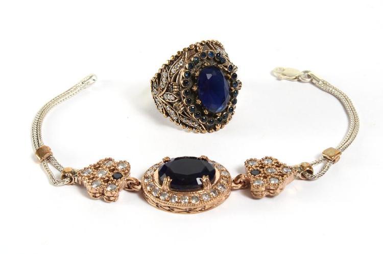 SAPPHIRE ''EXTRAORDINAIRE'' BRACELET & SAPPHIRE & WHITE TOPAZ RING - A prong set oval dark blue sapphire (approx, 15 mm x 12 mm) encir.