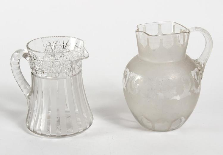 TWO CLEAR CUT AND ETCHED GLASS PITCHERS - One bulbous with a square neck and fluted handle, frosted but stenciled to leave clear plu...