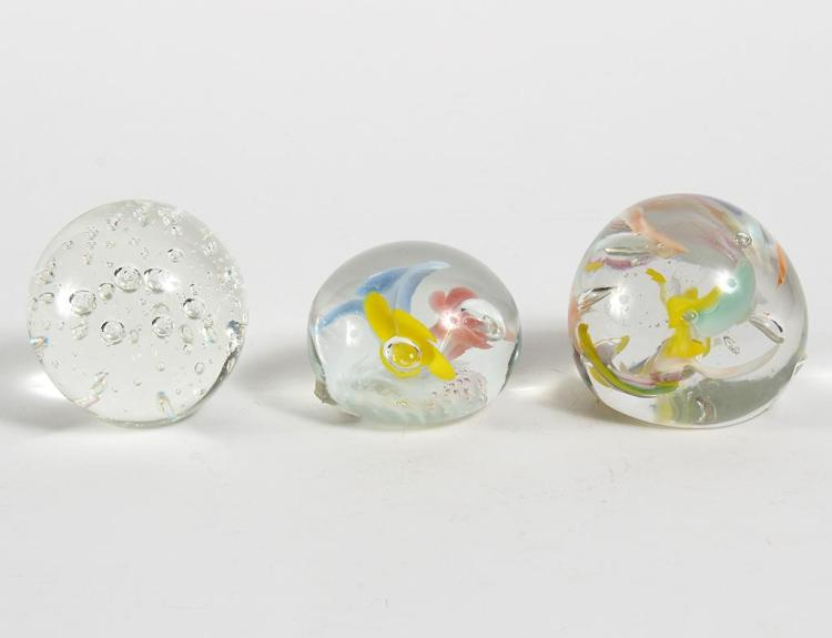 3 THICK GLASS GLOBE-SHAPED PAPERWEIGHTS - Includes a bubble glass globe paperweight, a 3 flower weight with colors yellow, blue, and...