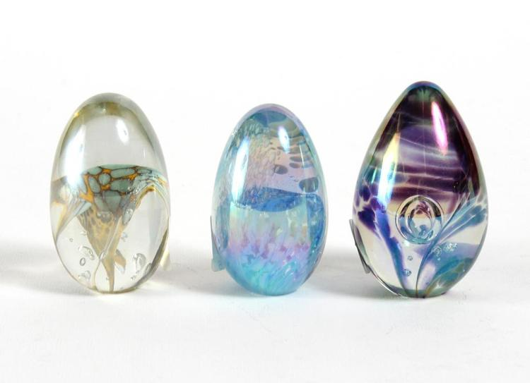3 EGG SHAPED PAPERWEIGHTS, MT ST HELENS AND GLASS EYE STUDIOS - 3 egg shaped paperweights with swirled and spotted color designs on...