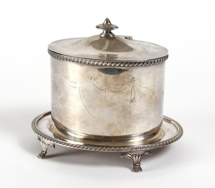 VICTORIAN SILVERPLATE BISCUIT BARREL - Oval body engraved with a shield and pendant foliage and with a gadrooned rim. Cover has a sp...