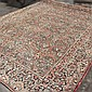 CARPET: HANDWOVEN PERSIAN SAROUK - Wool on a cotton warp with dense floral profusion on a pomegranate field surrounded by a miniatur...