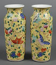 PAIR OF CHINESE PORCELAIN FAMILLE ROSE VASES - Cylindrical shape with a slightly flared neck. Jaune ground decorated with peaches, b...