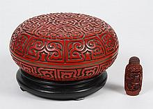 CHINESE CINNABAR SNUFF BOTTLE AND COVERED BOX - Snuff bottle has a chrysanthemum carving on stopper cap and landscape scene carved o...